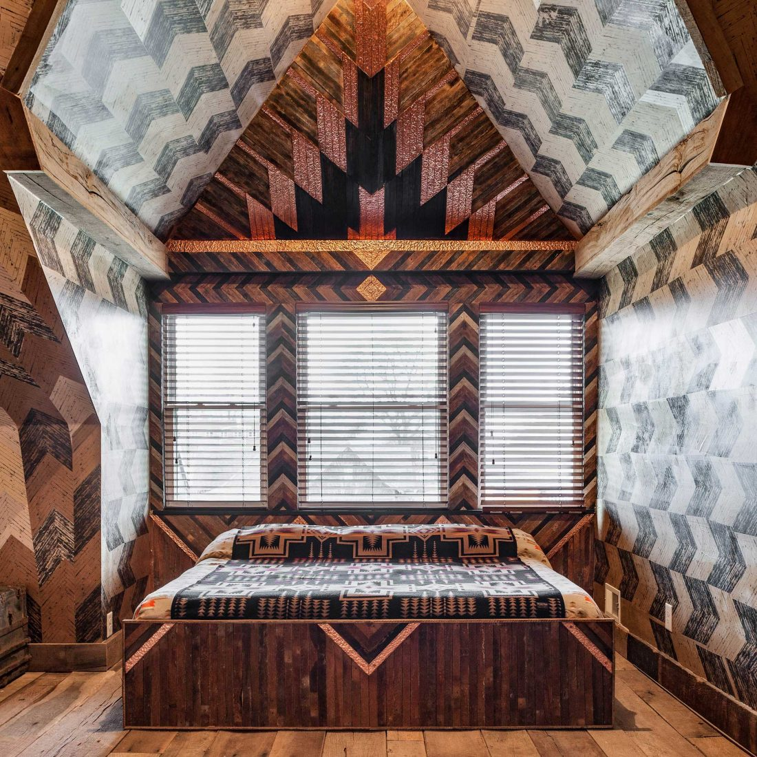 Queen sized bed inside The Lions Den room of Urban Cowboy Nashville. The bed is placed in a cozy area of this Penthouse room, with a 14 foot wooden headboard. Photo taken by Ben Fitchett.