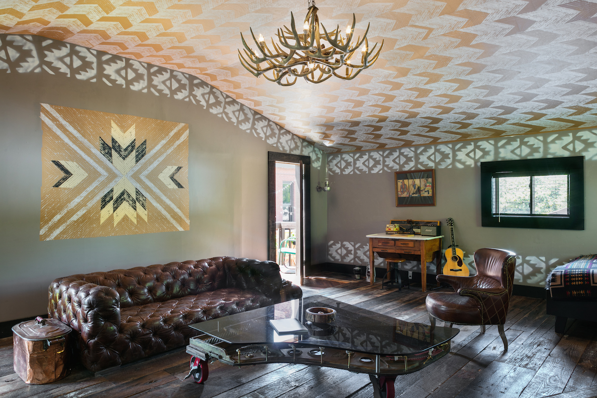 View of a living room inside The Cabin accommodations of Urban Cowboy Nashville. There is a large brown couch beneath artwork on the wall. A table sits low, a clear surface curved in the shape of a grand piano.