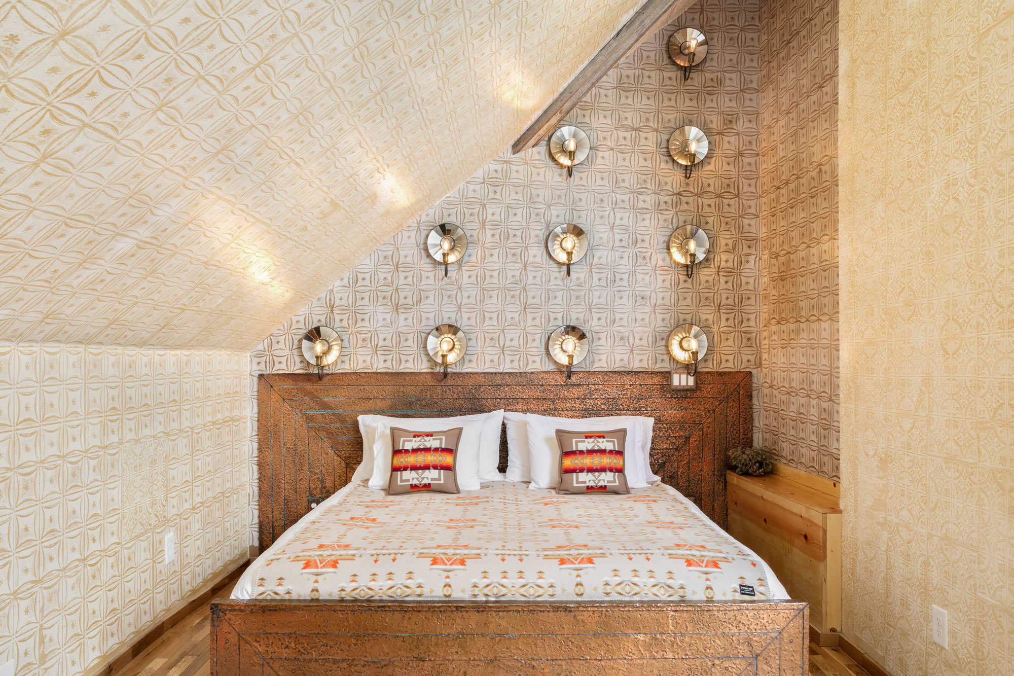 Front shot of the king sized bed framed in the A-frame roofing of Urban Cowboy Nashville. A triple switch is located in the wall beside, controlling the styled bulb lighting above.