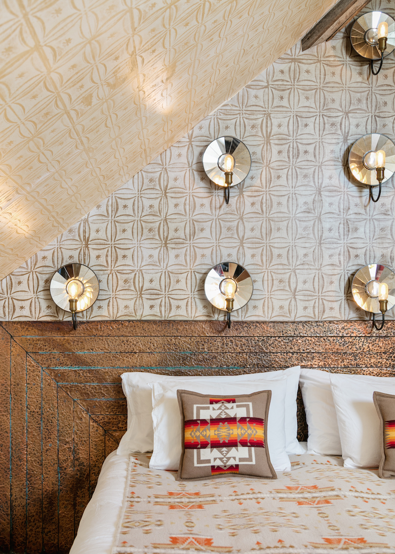 Cropped, front shot of the king sized bed inside The Muse guest room of Urban Cowboy Nashville. Reflective surfaces are attached to the wall, with a light bulb in front of each one.