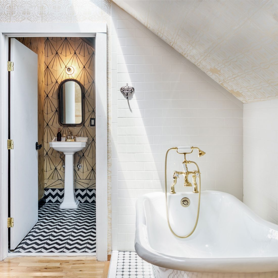 Sleek white bathtub under the A-frame of The Urban Cowboy Nashville. Beyond the bathroom, a door leads to a tiled wash room.