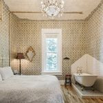 The Victorian Room inside Urban Cowboy Nashville, lit with a warm light of the chandelier. A king sized bed is placed in the middle, just across from a tiled area holding a claw foot bathtub.