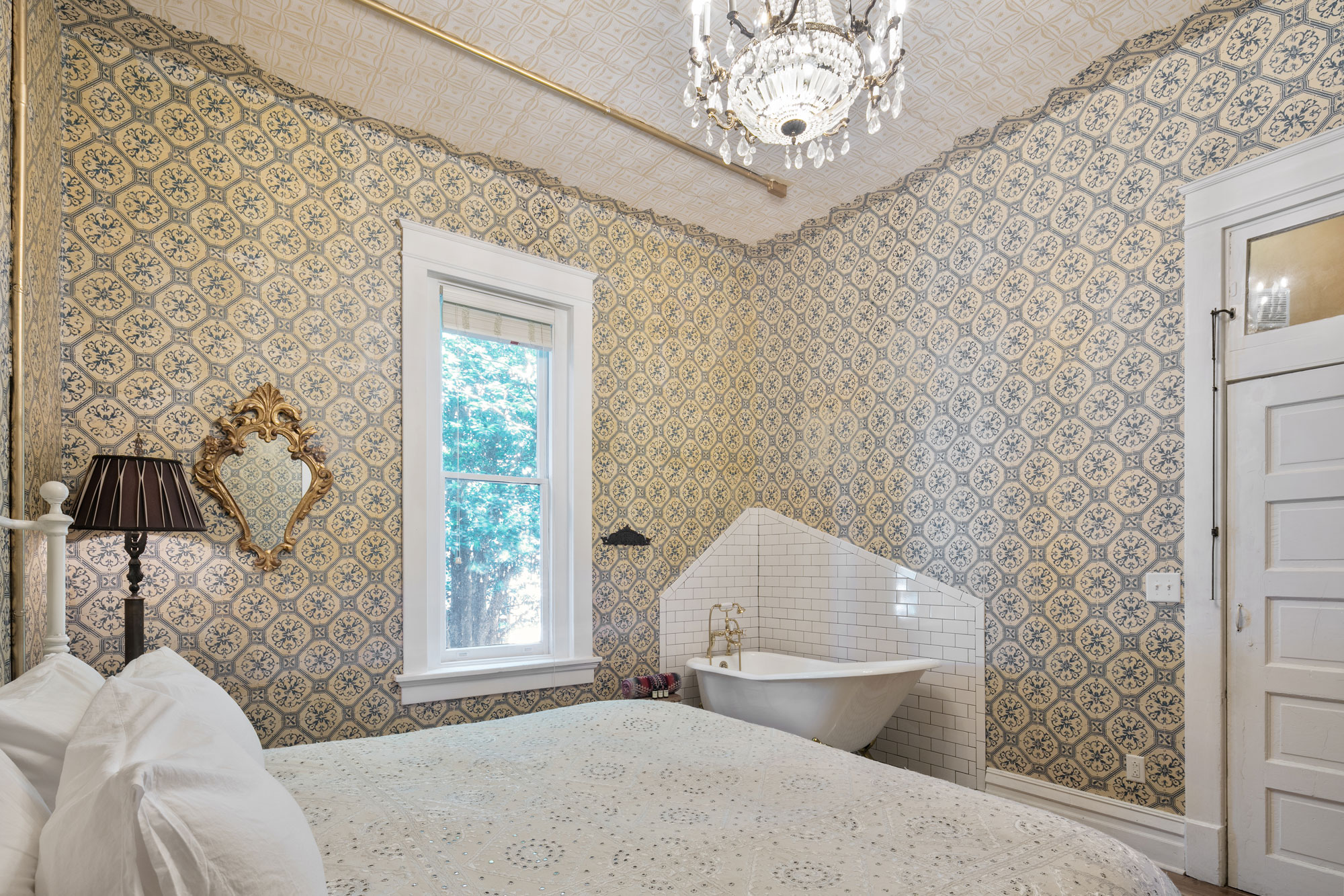 View from beside the king sized bed inside The Victorian Room of Urban Cowboy Nashville. Across from you is a tiled corner, holding a claw foot bathtub. A Victorian floor lamp is near the window, alongside a matching wall mirror.