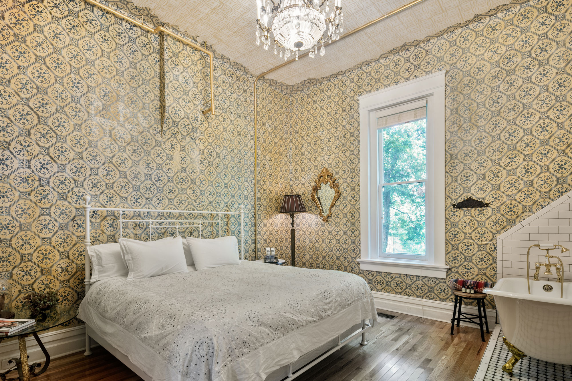 The Victorian Room inside Urban Cowboy Nashville. A king sized bed is placed in the middle, just across from a tiled area holding a claw foot bathtub. The walls are tiled with detail and a chandelier lamp gives a warm light