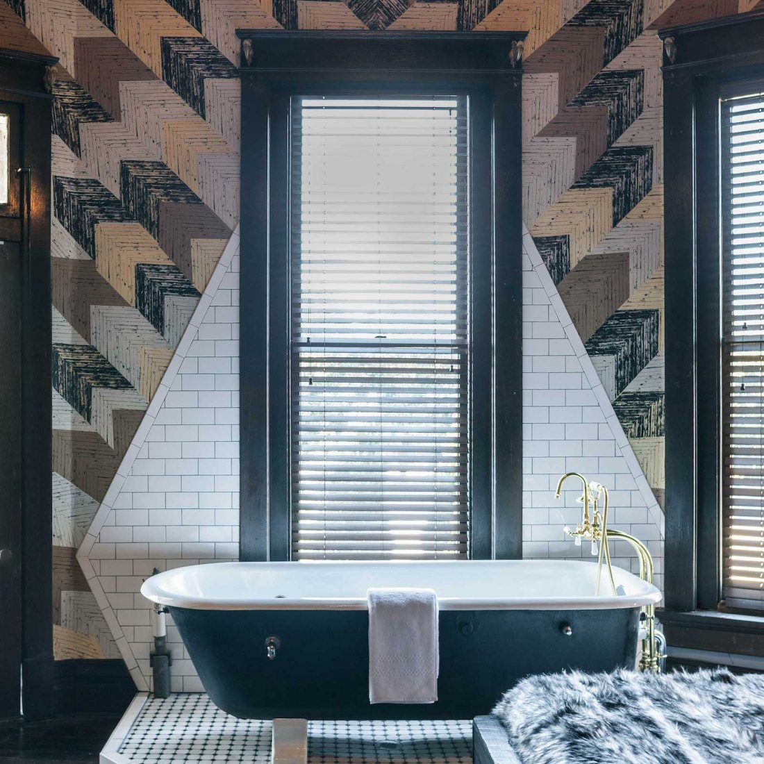 View of a bathtub inside The Midnight Rider accommodation inside Urban Cowboy Nashville. The tub is near the king sized bed, placed atop a tiled area shaped like a diamond along the wall. This octagonal room is set with three tall windows.
