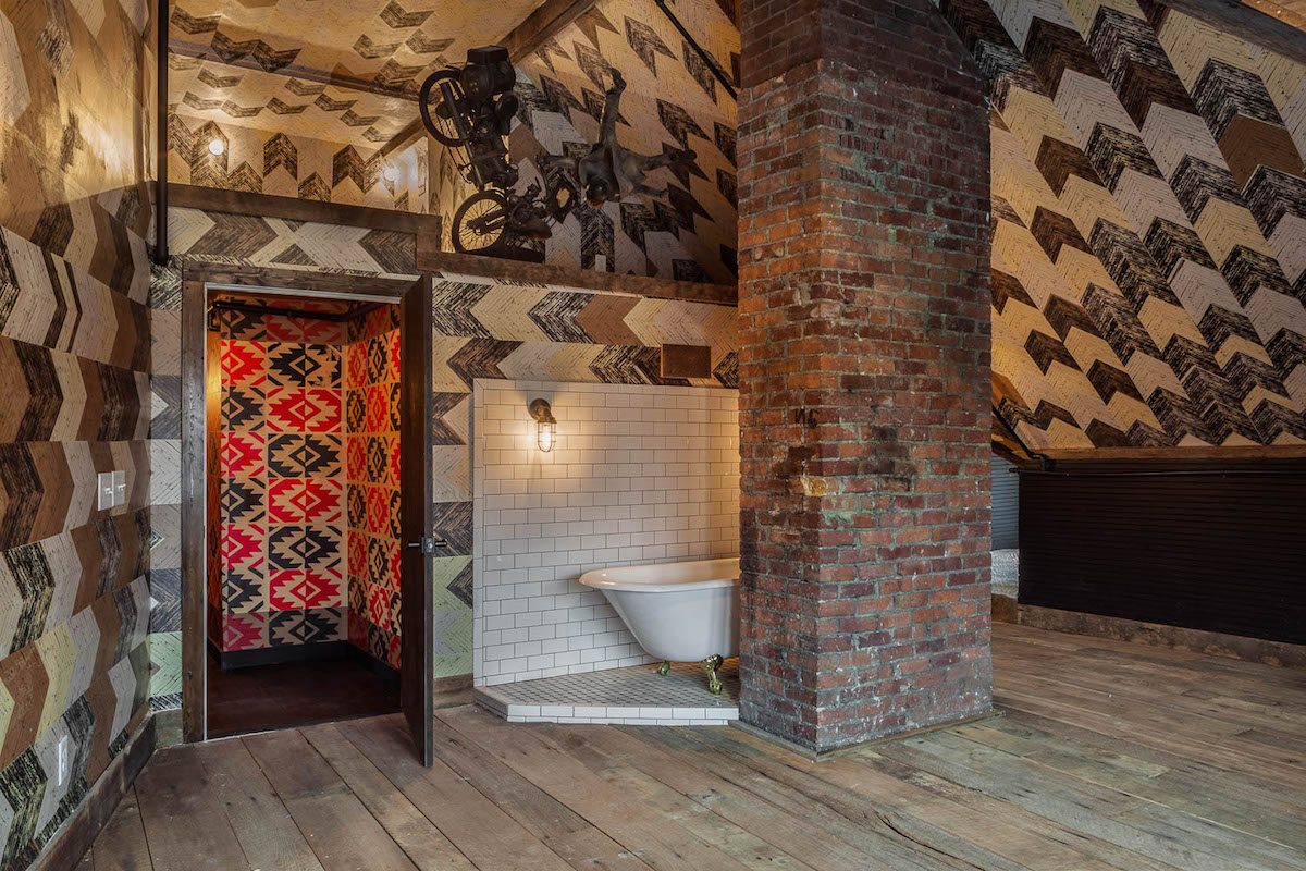 Bathroom and Tub Area of The Lions Den room of Urban Cowboy Nashville. A vibrant pattern of the sink and toilet room can be seen through an open door. To the right, a clawfoot tub is placed just behind this gabled room's beam. Photo taken by Ben Fitchett.