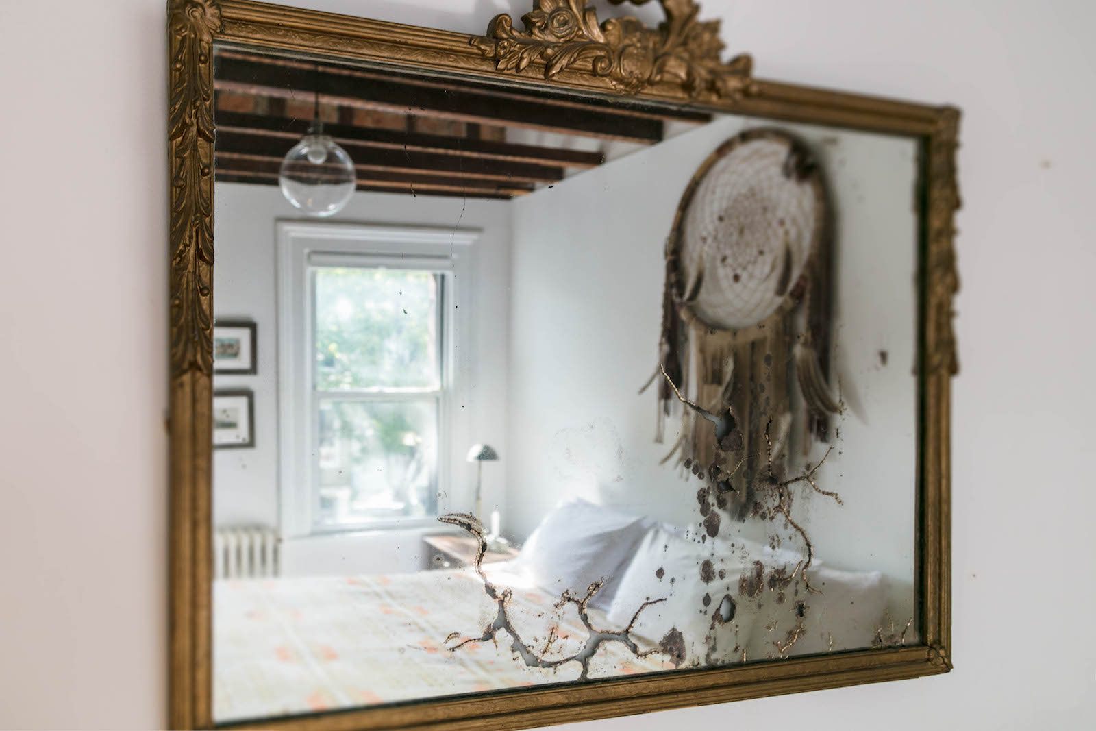 The Dream Catcher's king sized bed reflected in a framed mirror of this Urban Cowboy Brooklyn accommodation. A window looks out to trees.