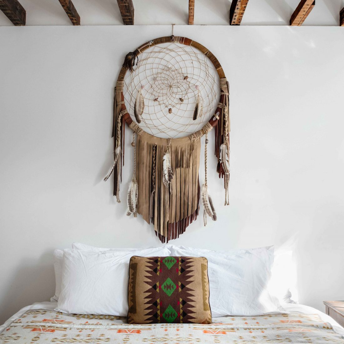 King sized bed inside the Dream Catcher room of Urban Cowboy Brooklyn. A large fringed dreamcatcher hangs above the bed.