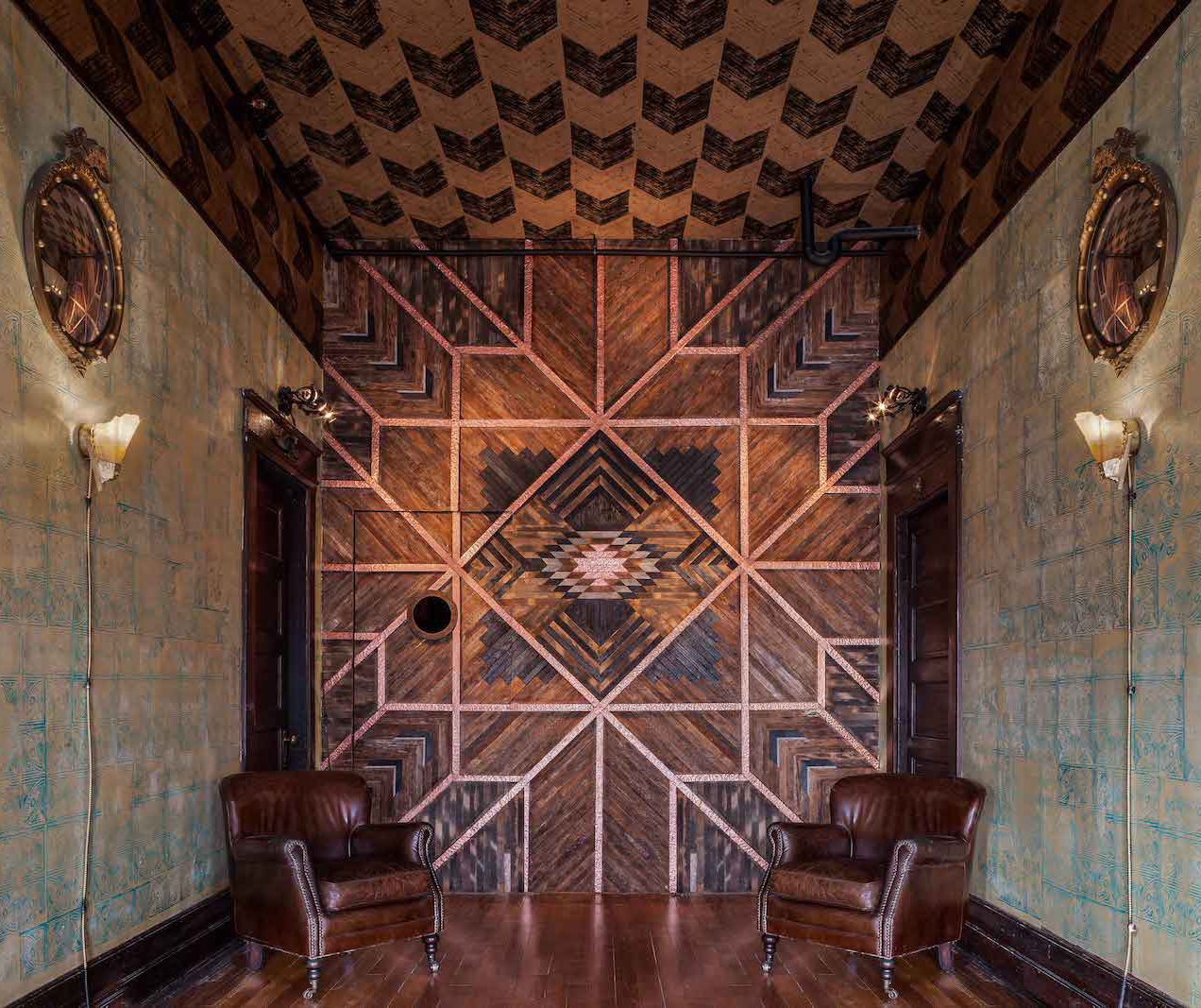 Look into the foyer of Urban Cowboy Nashville. Breaking up a soft patterned wall is warm linework in a Southwestern motif.