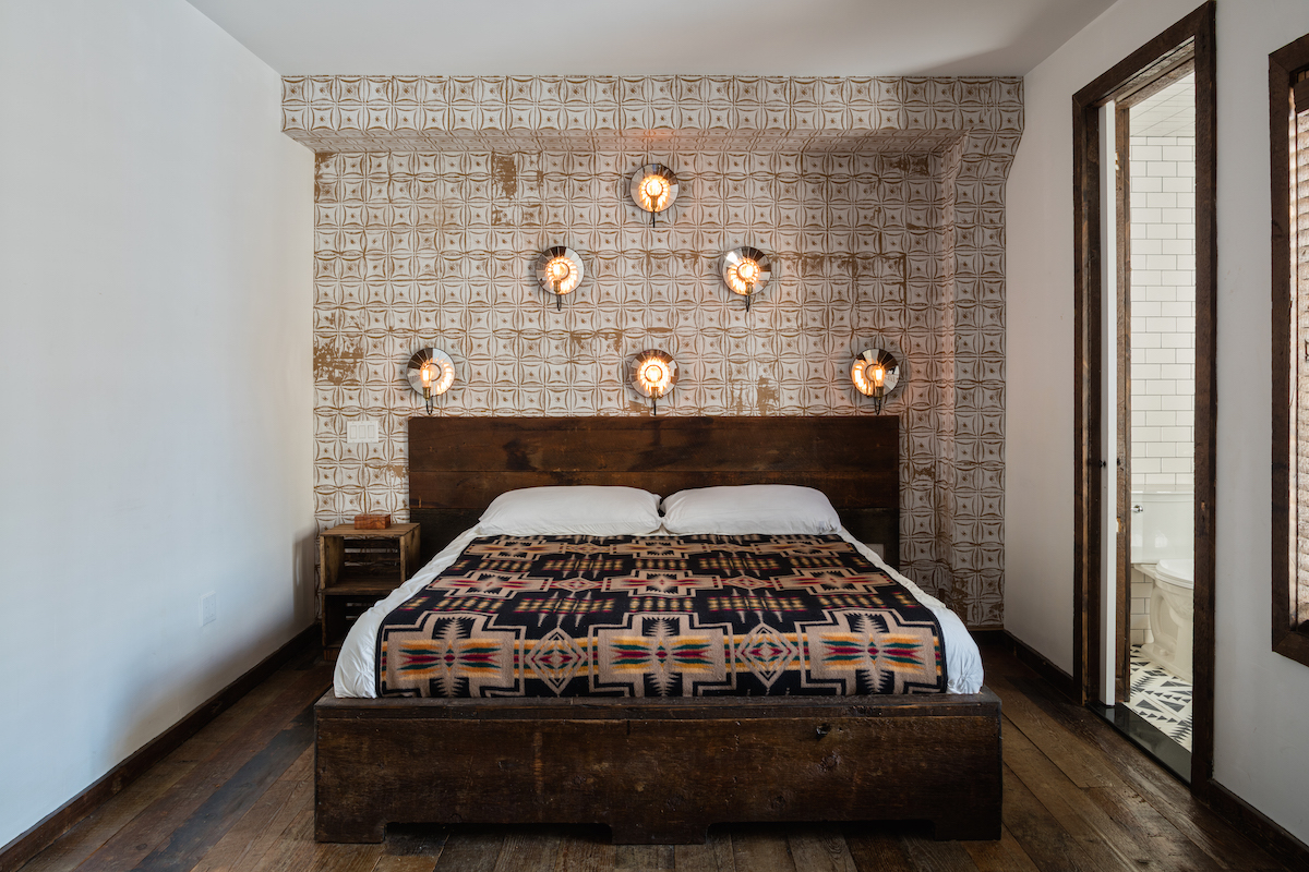 Queen sized bed in one of the bedrooms of Urban Cowboy Brooklyn's private townhouse. This area of the Treehouse offers a bathroom, just off to the side of this room. Six light bulbs are mounted in decorated wall mounts above the bed.