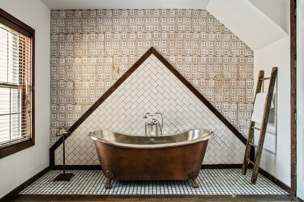 The clawfoot bathtub of the Private Treehouse townhouse inside Urban Cowboy. The tilework makes a triangle on the wall, where the claw foot bathtub rests.