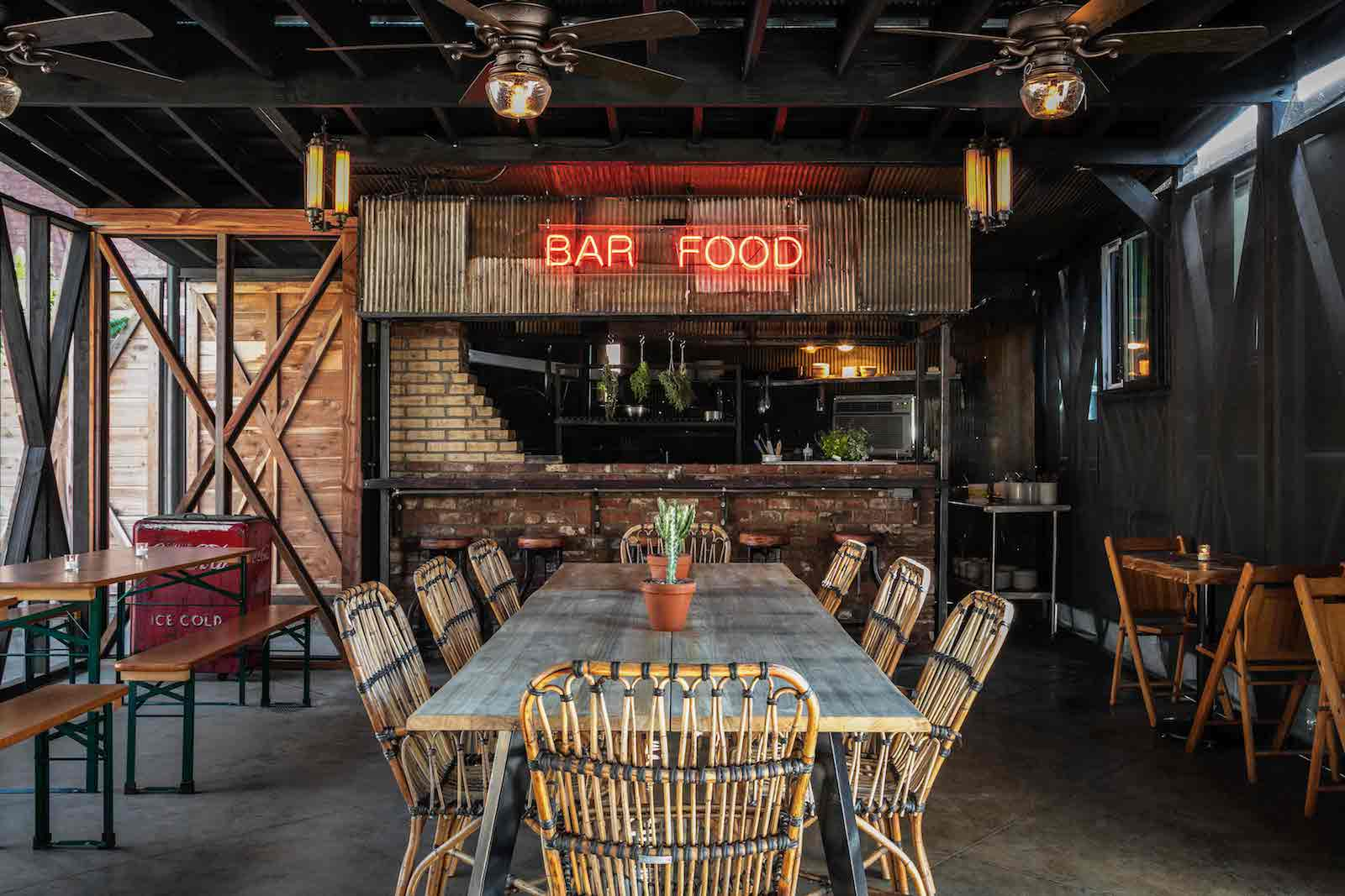 View of the main dining area of Urban Cowboy's Public House Kitchen and Bar. Woven chairs make up the area in the center, with wooden benches and tables in the areas beside.