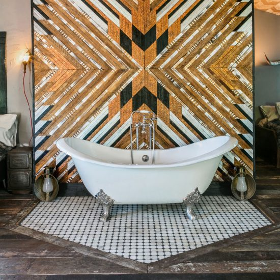 The clawfoot bathtub of The Cabin, inside Urban Cowboy. Geometric shapes are worked into gold reflective shapes behind.