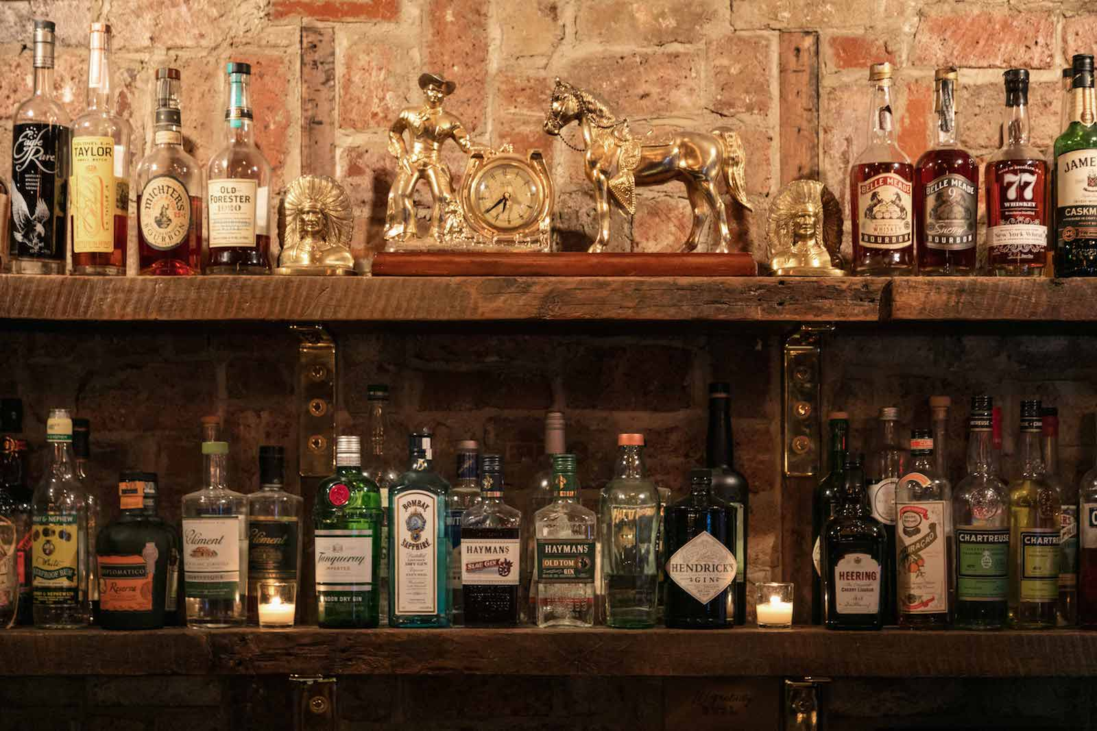 Shelves holding alcohol behind the bar of Urban Cowboy Nashville's Public House. Golden sculpture makes up the center of the top shelf.